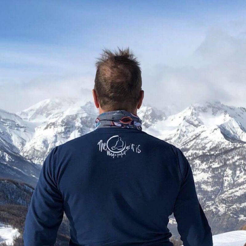A snow capped mountain shot of a man wearing the Zen wisdom t-shirt 'The Way Is Perfect As It Is.'