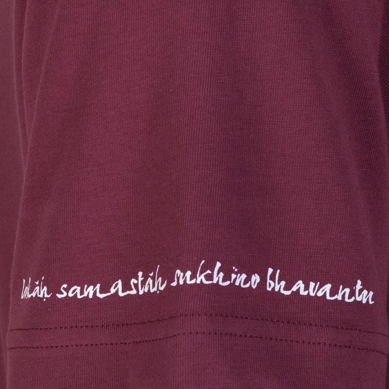 Detail of the words 'Lokah Samastah Sukhino Bhavantu' hand screen printed on the edge of the sleeve hem in white ink.