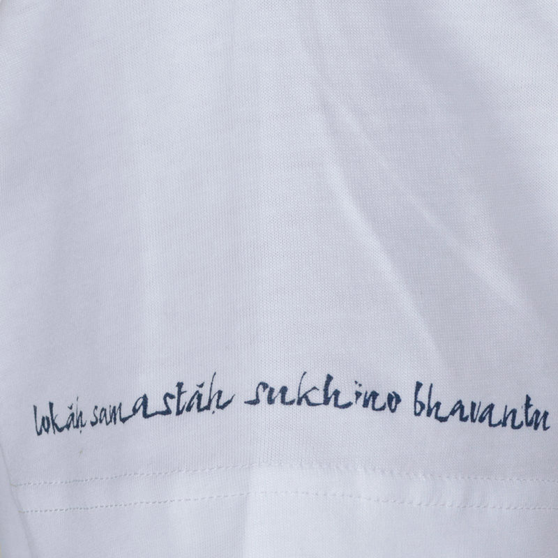 Detail of the words 'Lokah Samastah Sukhino Bhavantu' hand screen printed on the edge of the sleeve hem in navy ink.