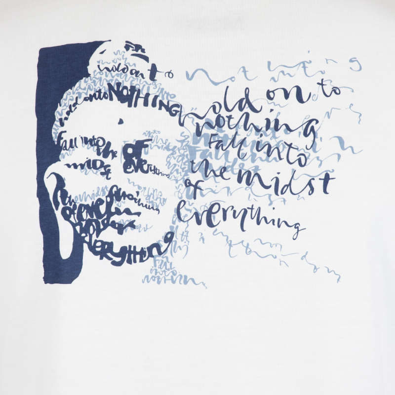 Detail of the graphic T-shirt that shows the face of Buddha created from calligraphy that says 'Hold on to Nothing & Fall into the Midst of Everything.'