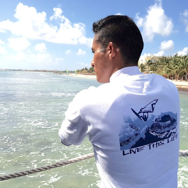 A young man at the beach wearing a windsurfer and karma yoga organic t-shirt with the mindfulness slogan 'live this life like it's your last'