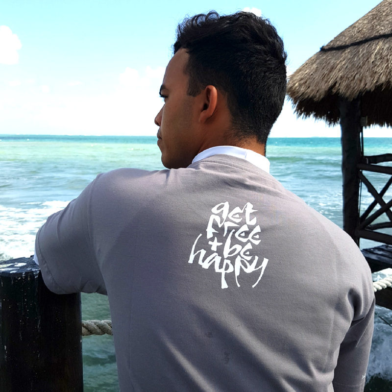 The back of the fossil grey Sanskrit inspired T-shirt Lokah Samastah Sukhino Bhavantu, showing the back neck print that says 'get free & be happy.'