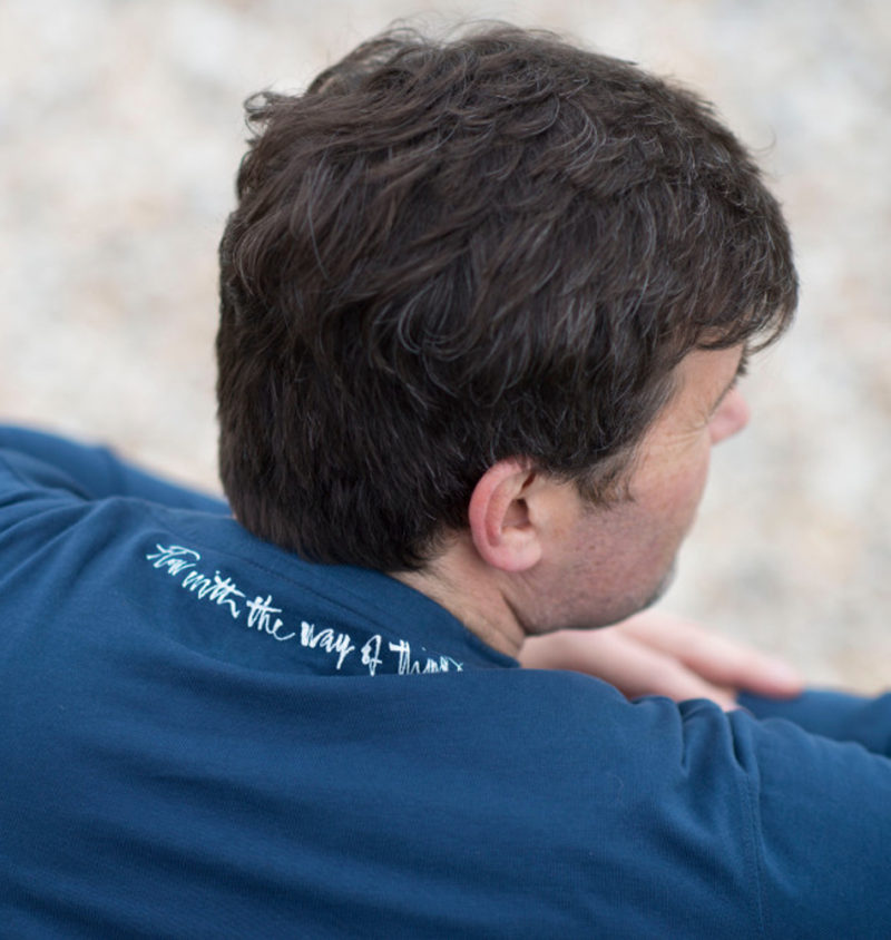 The back of a man wearing a navy, long sleeve T-shirt on the neck of which the words 'flow with the way of things,' has been printed in white ink