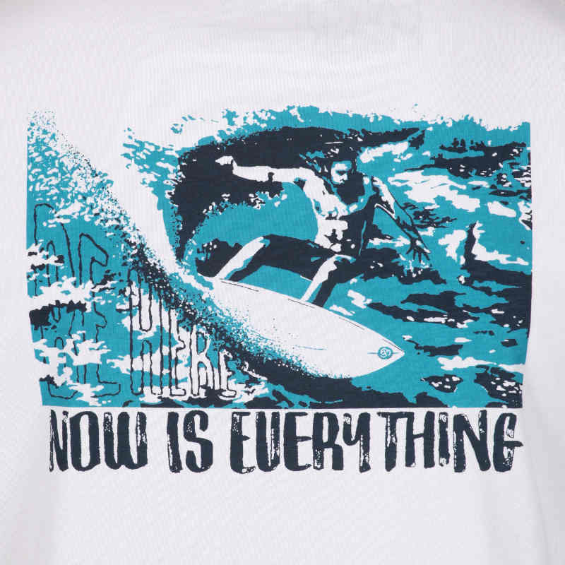A detail of the graphic of the surfing and mindfulness t-shirt 'be here, now is everything.'