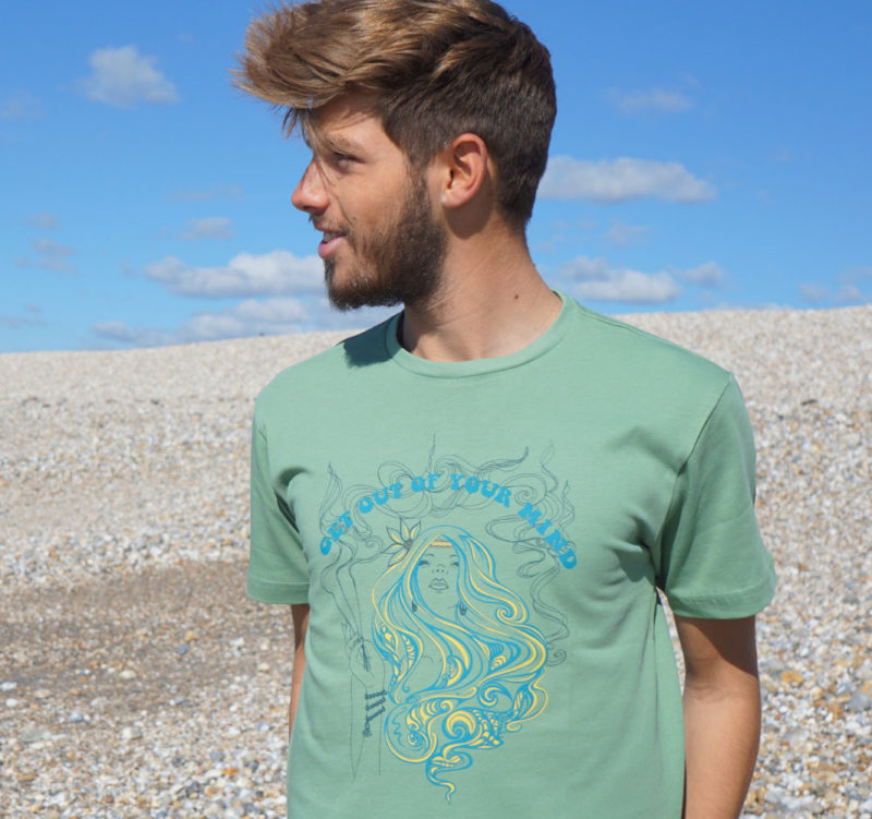 A young man on the beach wearing a sage green Osho inspired mindfulness T-shirt, 'get out of your mind.'