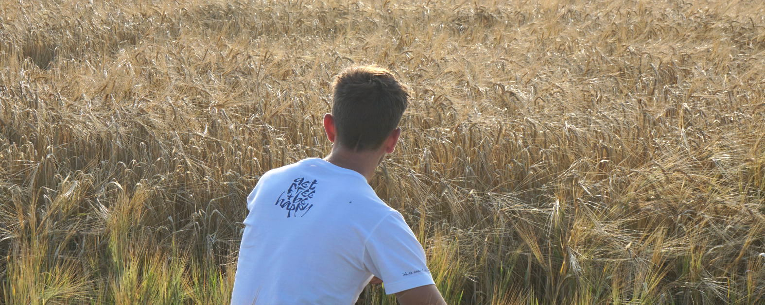 A cornfield photo of the back of a young man the white Sanskrit inspired T-shirt Lokah Samastah Sukhino Bhavantu, showing the back neck print that says 'get free & be happy.'