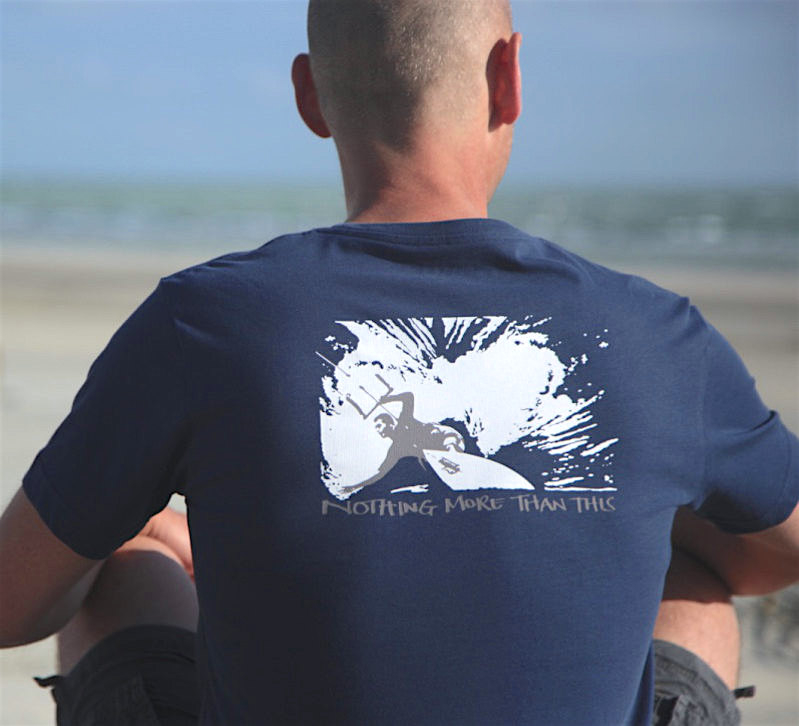 A man sitting on the beach wearing a graphic T-shirt of a kitesurfer with the mindfulness phrase 'Nothing More than This'